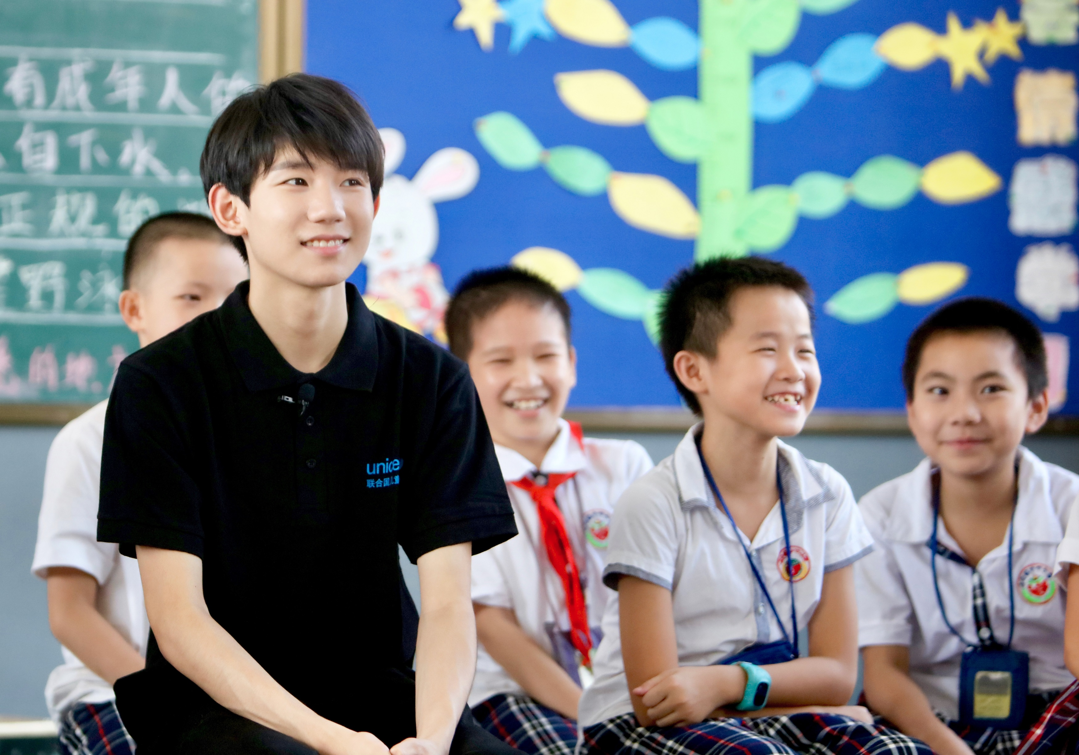 Chinese youth icon Wang (Roy) Yuang sits with school children in a classroom