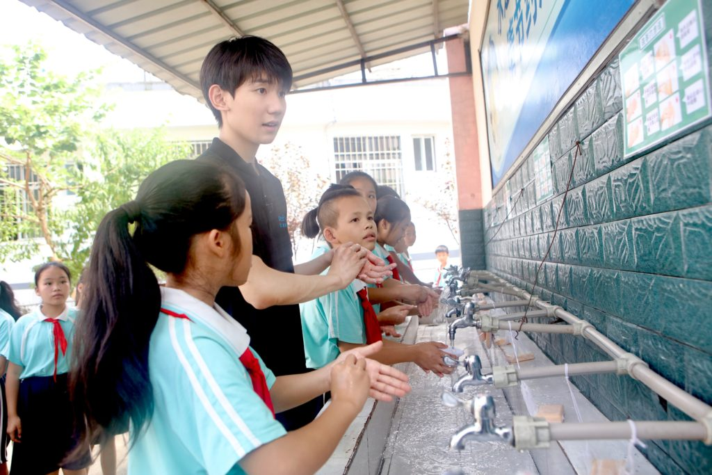 UNICEF Special Advocate for Education Wang Yuang and some young children wash there hands at a school.