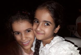 Two girls huddled together, smiling as they face the camera