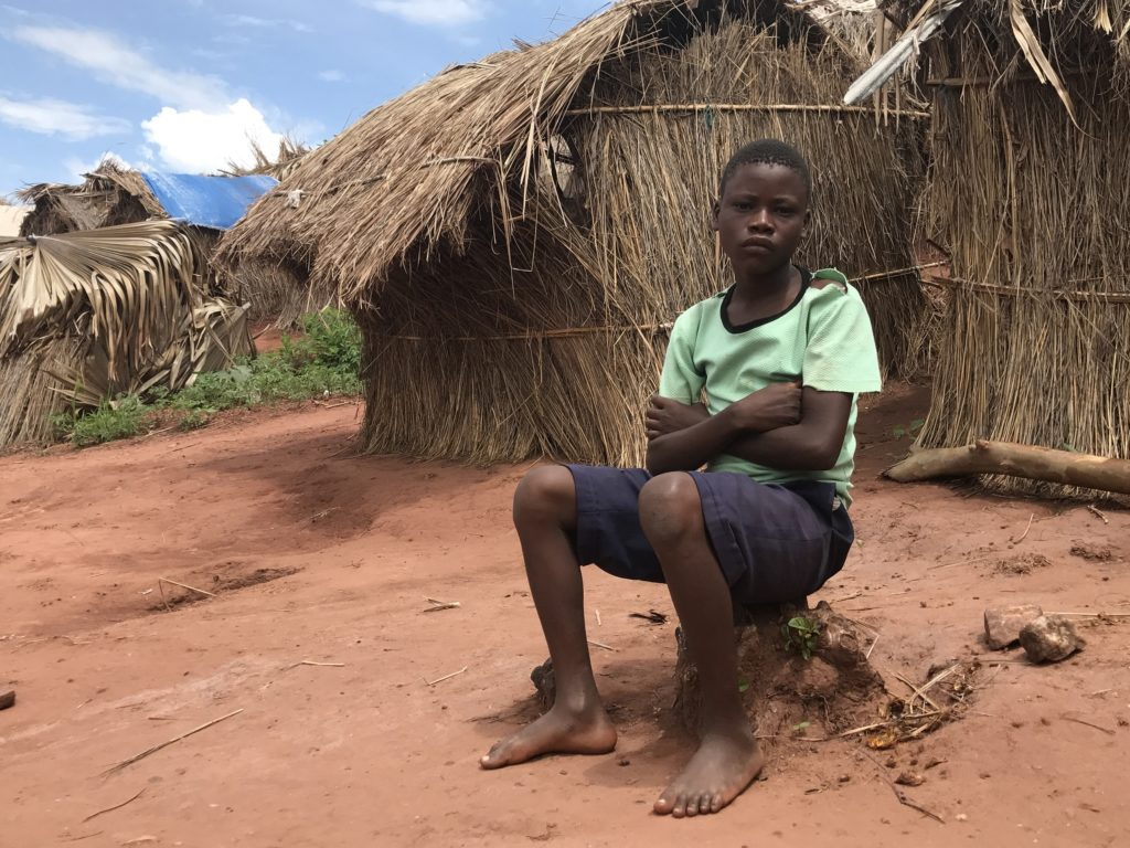 Boy sitting in front of a hut