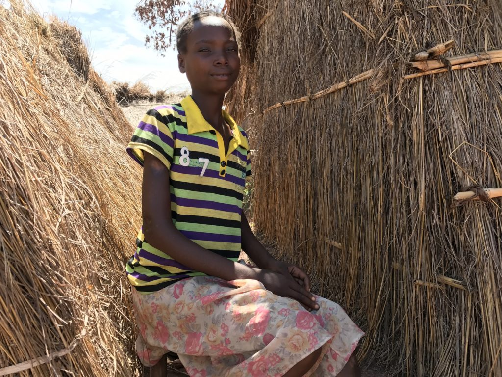 Girl sitting outside and in front of her thatched hut.