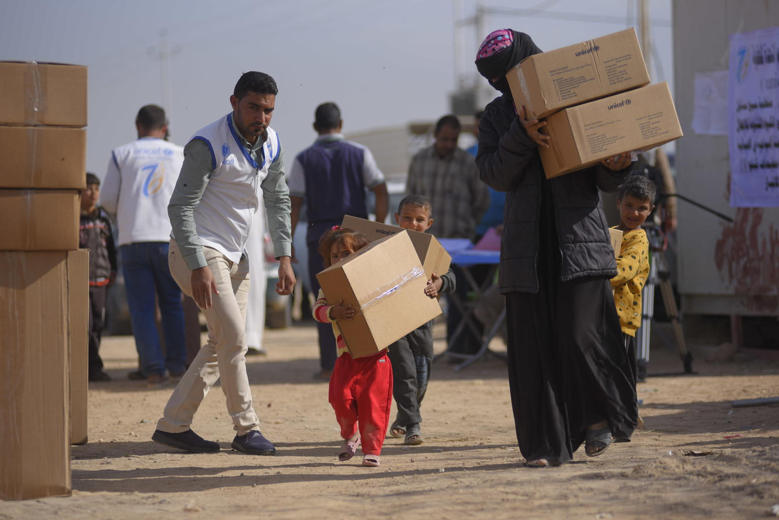 A women and some children carry boxes as a UNICEF volunteer looks on.