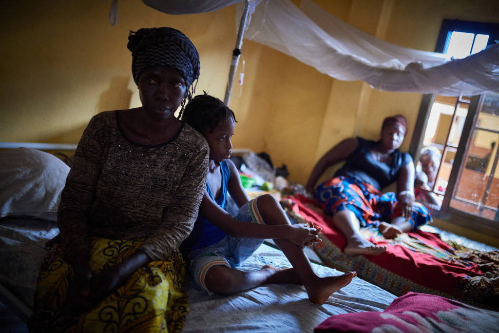 A mother sits with her child on a hospital bed with another malaria patient under a mosquito net behind them