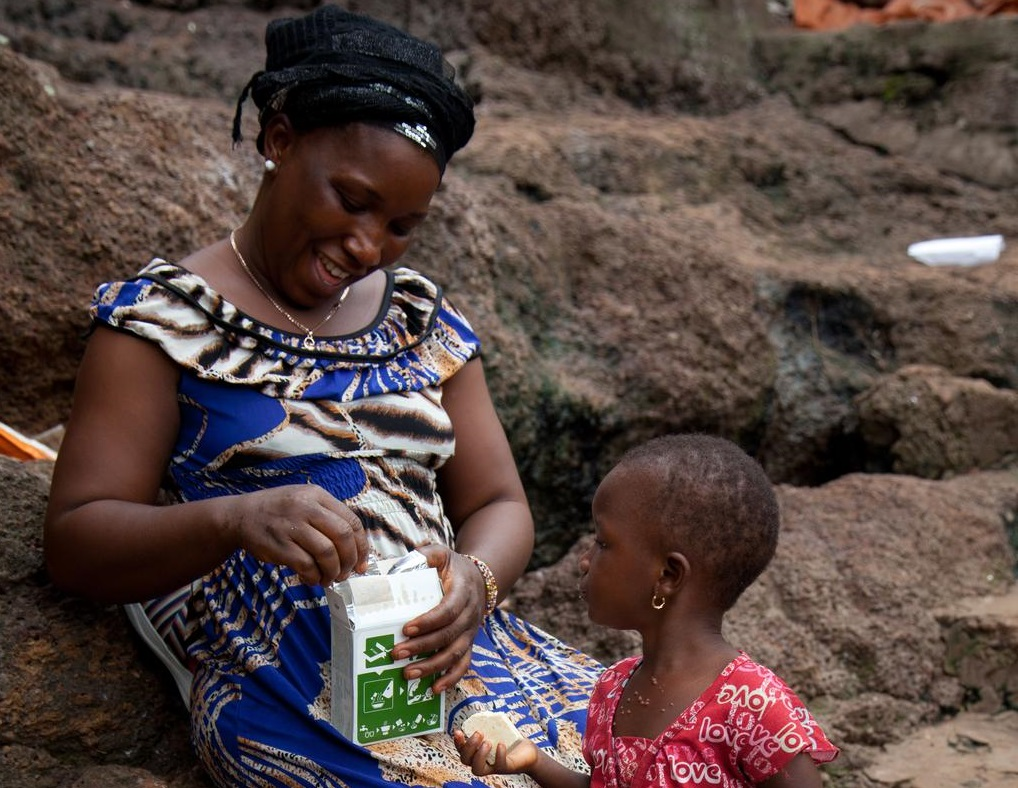 A mother and child looking at the white packages they are holding