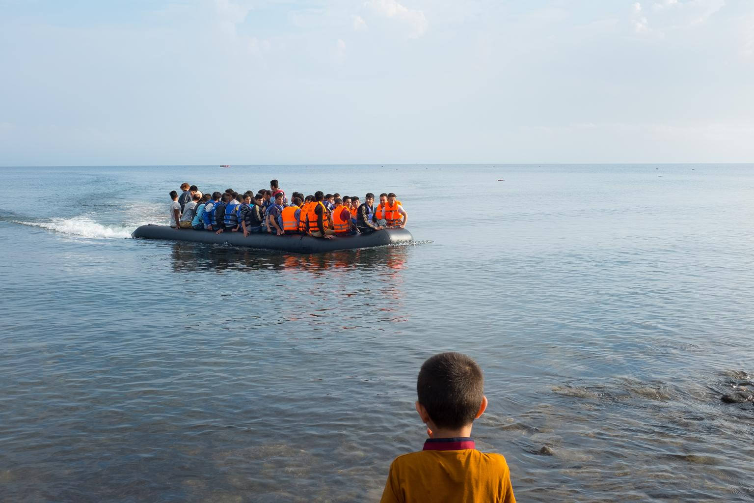 A boy with his back to the camera watches a boat filled with people as it comes ashore