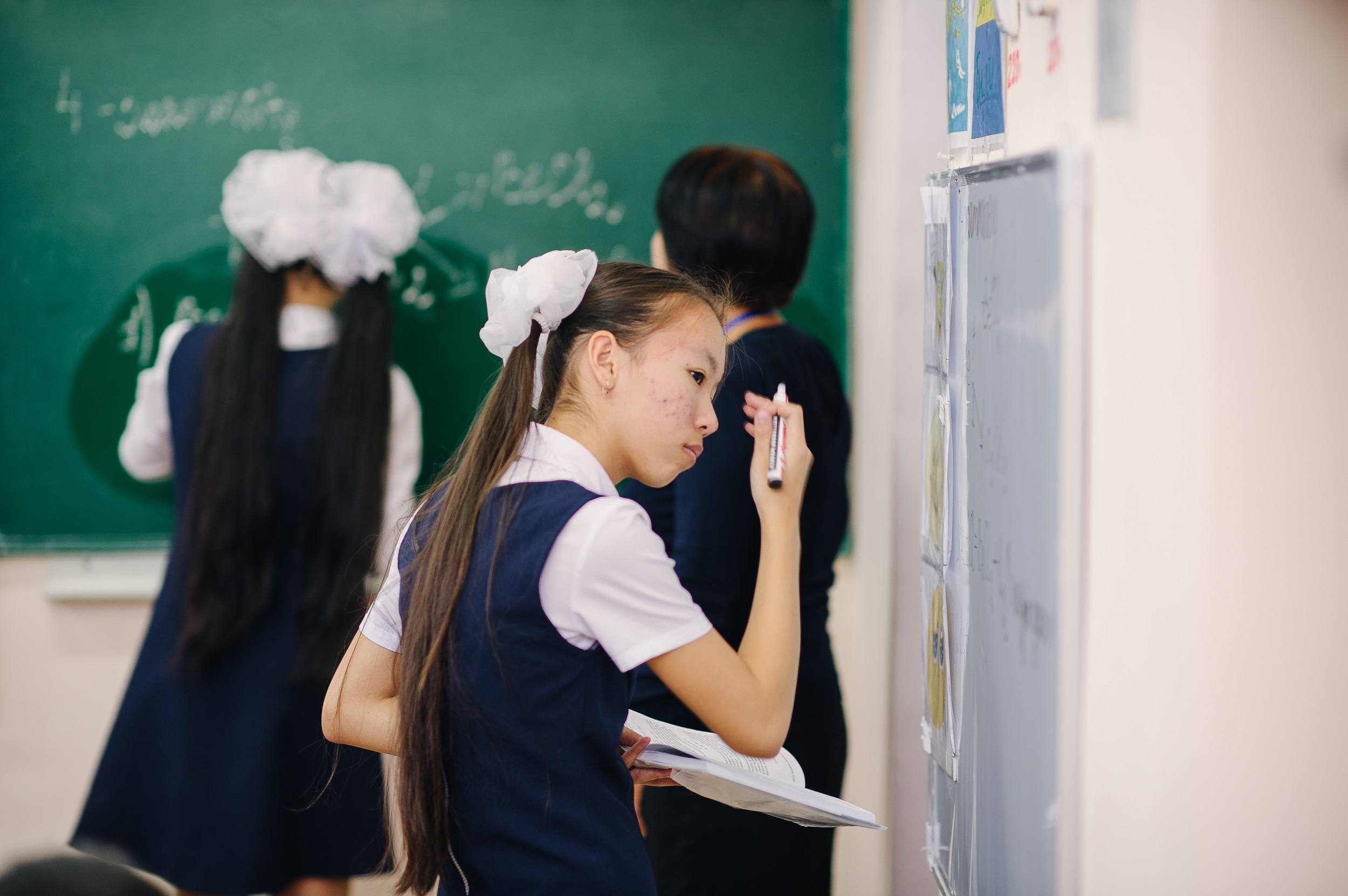 School girl in a classroom holds a marker pen as she stands looking at a classroom whiteboard
