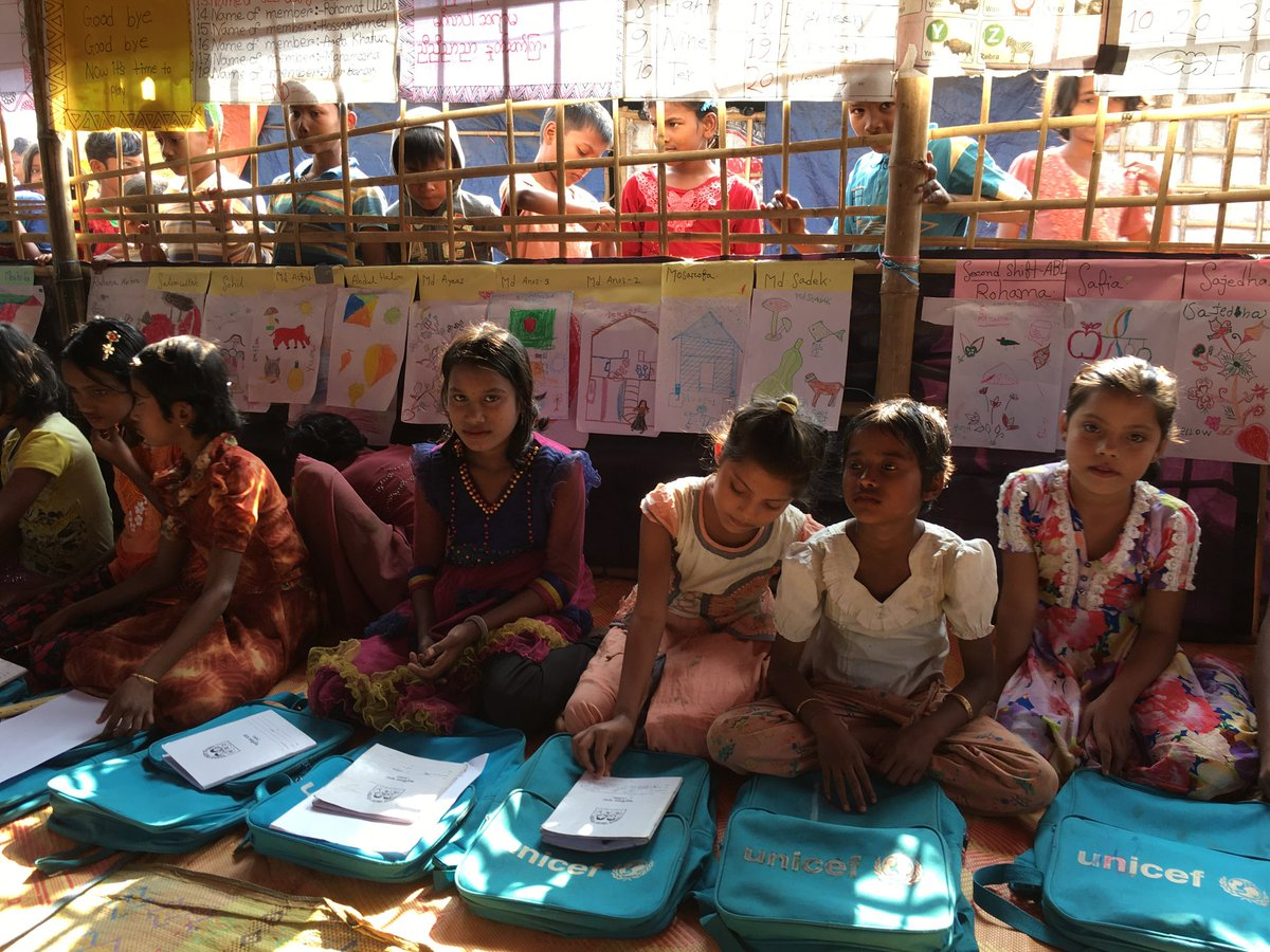 Children sitting in a row on the floor with open books in front of them