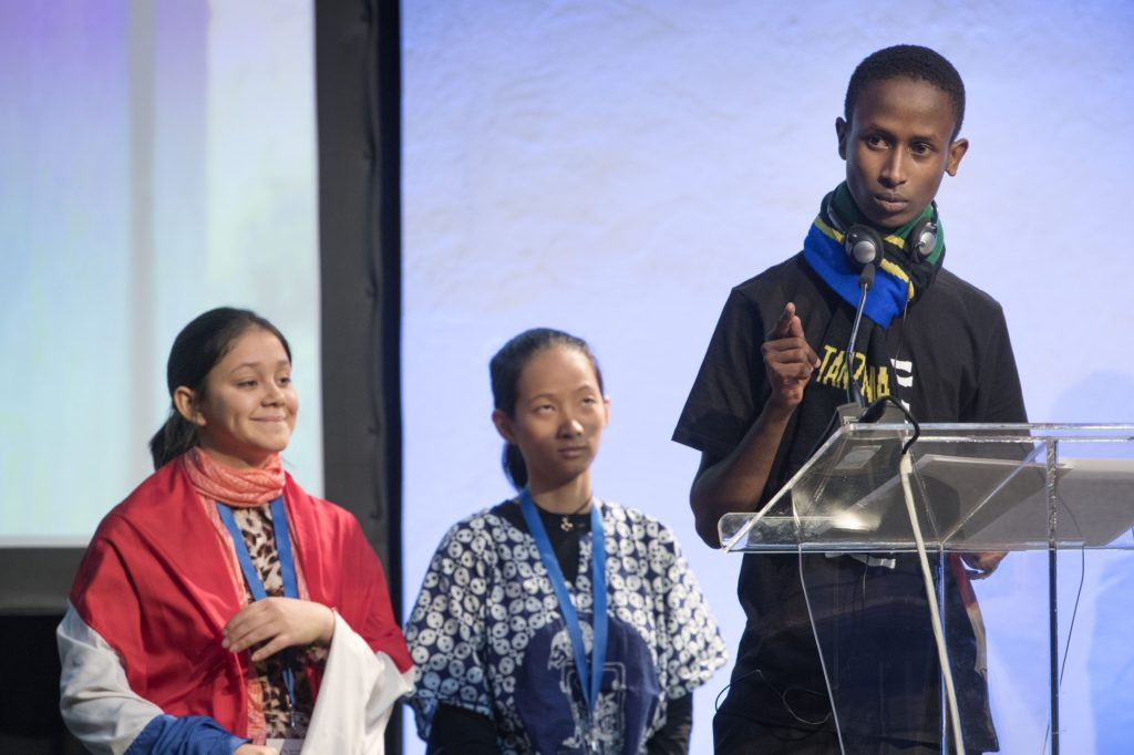 A teenager addreses an audience from behind a podium with two teenage girls looking on