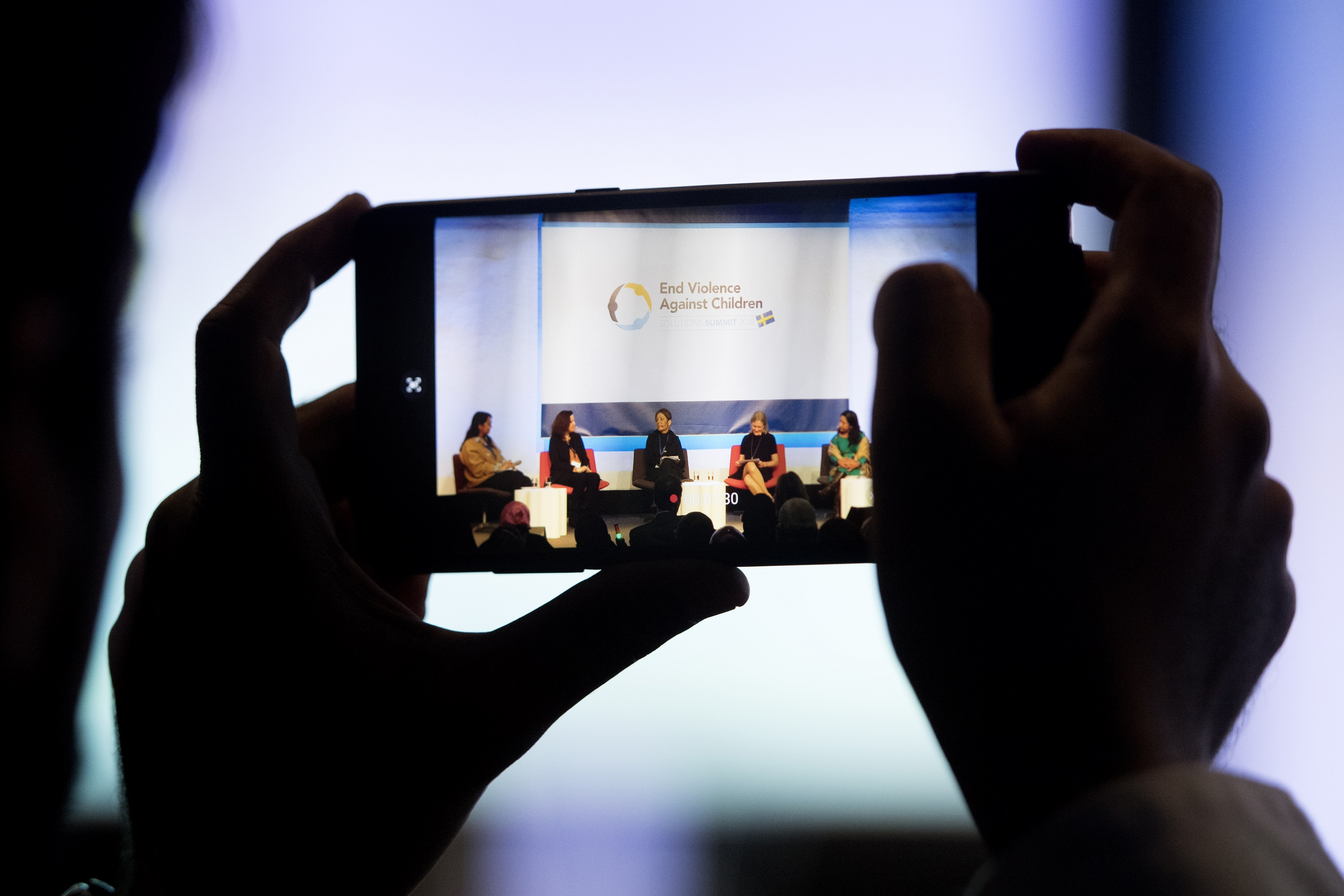 A panel of speakers sitting under a sign stating: End Violence Against Children, as seen through the view finder of a camera phone