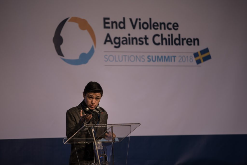 A teenage boy addresses an audience from behind a podium on a stage that features words on a back drop behind him stating: End Violence Against children, Solutions Summit 2018