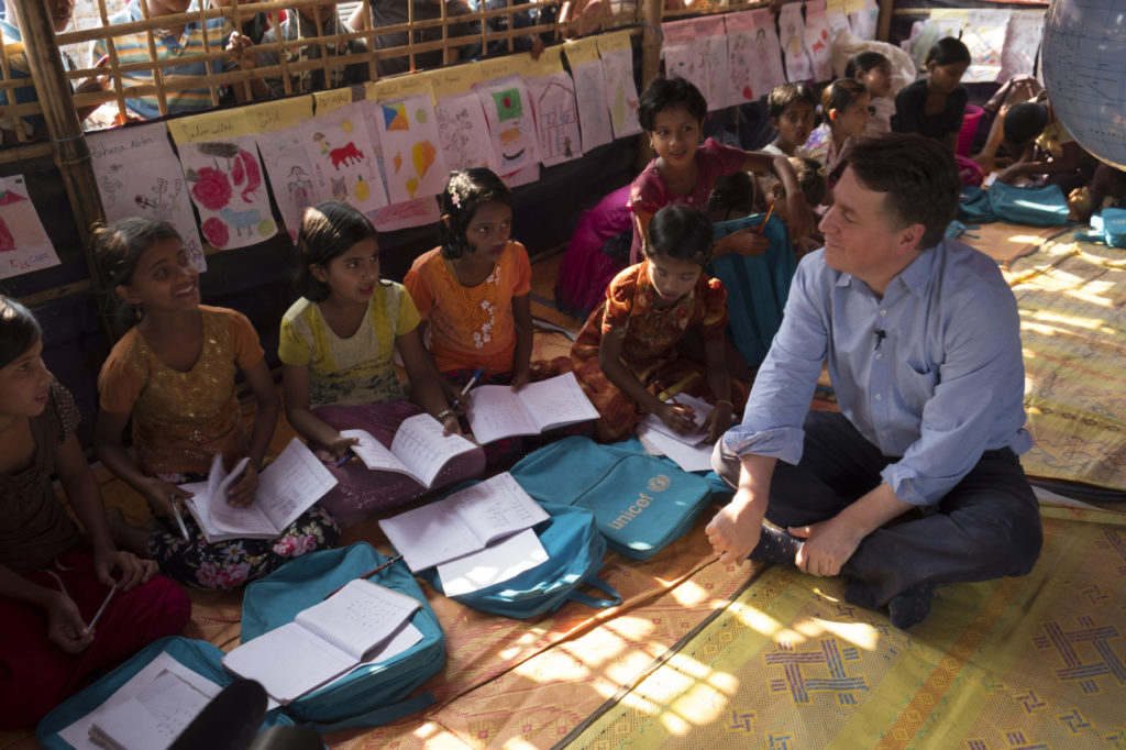 A group of children with workbooks sitting on the floor and talking to a visiting man