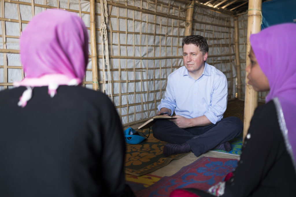 Man sitting on ground with taking notes while talking to two women