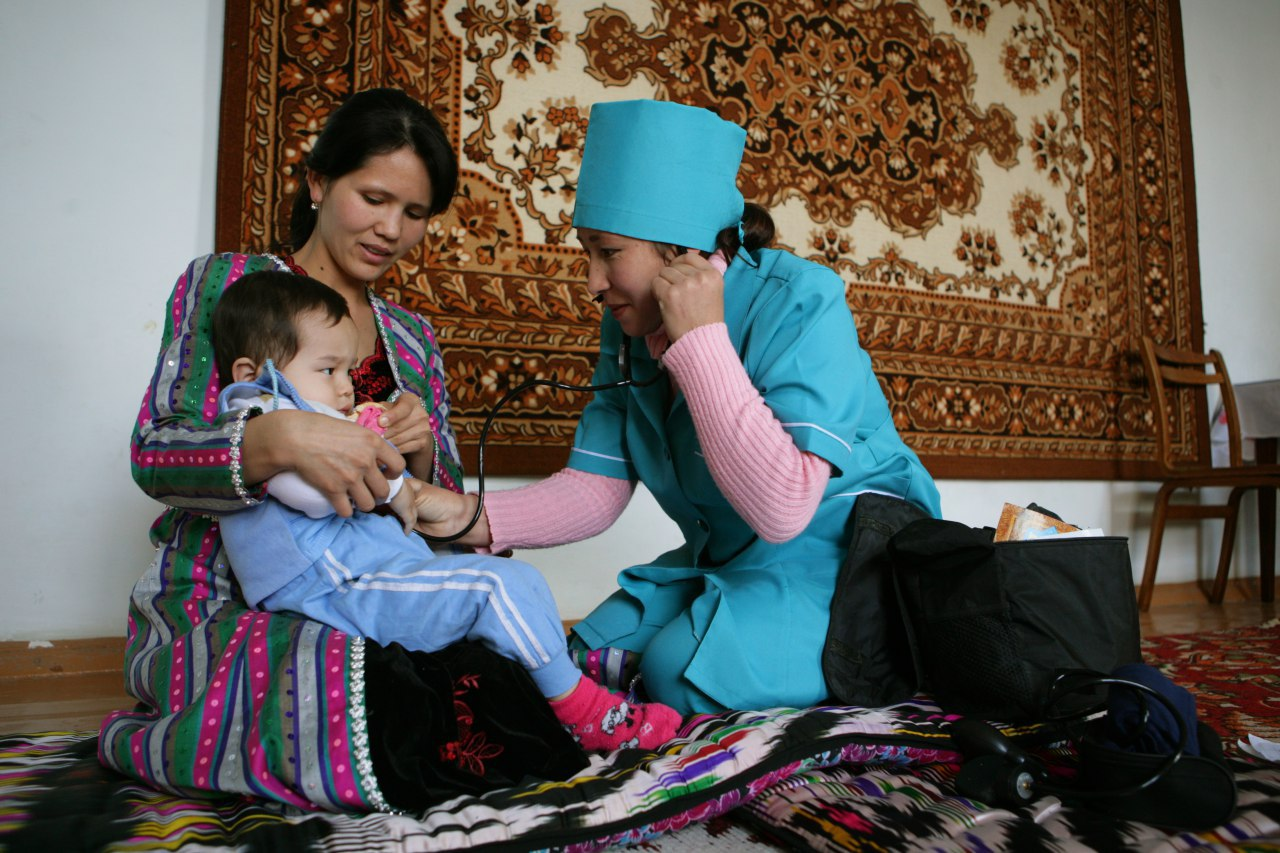 A nurse with a stethoscope kneels to check on a child sitting on his mother's lap.