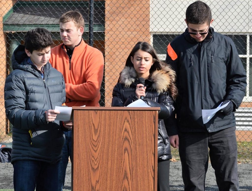Four teenagers stand behind a podium and read statements from papers they are holding.