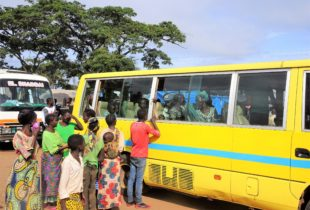 People standing outside a departing yellow bus interact and gesture to people on the bus in Zambia.