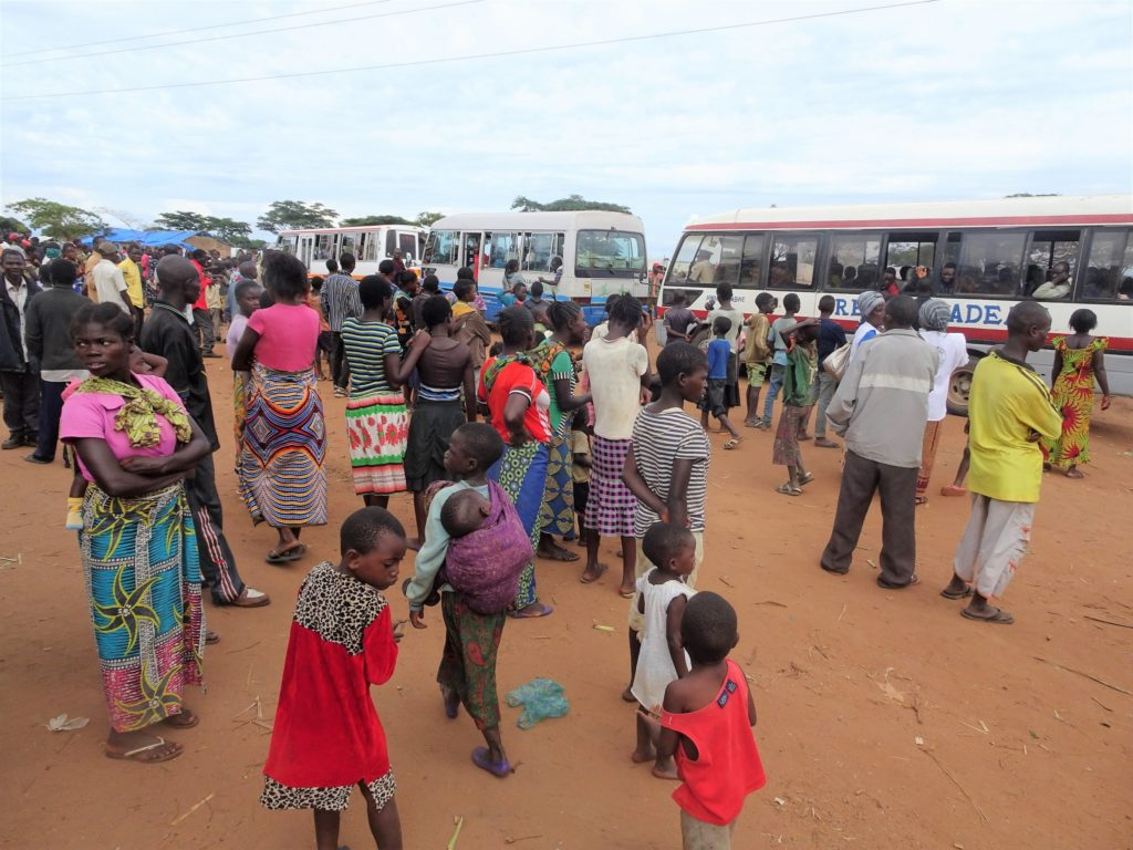 People gather around a row of buses at a resettlement camp in Zambia.