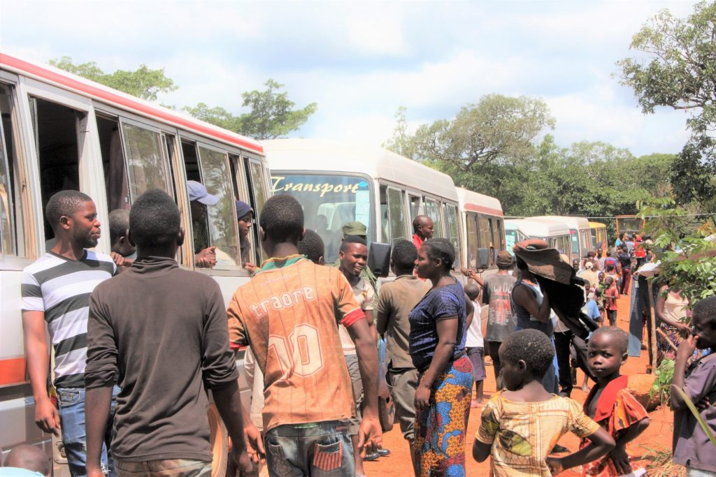 People gather together alongside a row of departing buses in a refugee settlement camp Zambia.