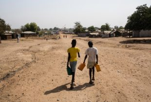 Two girls, carrying cans, walk away from the camera, down a dusty road.