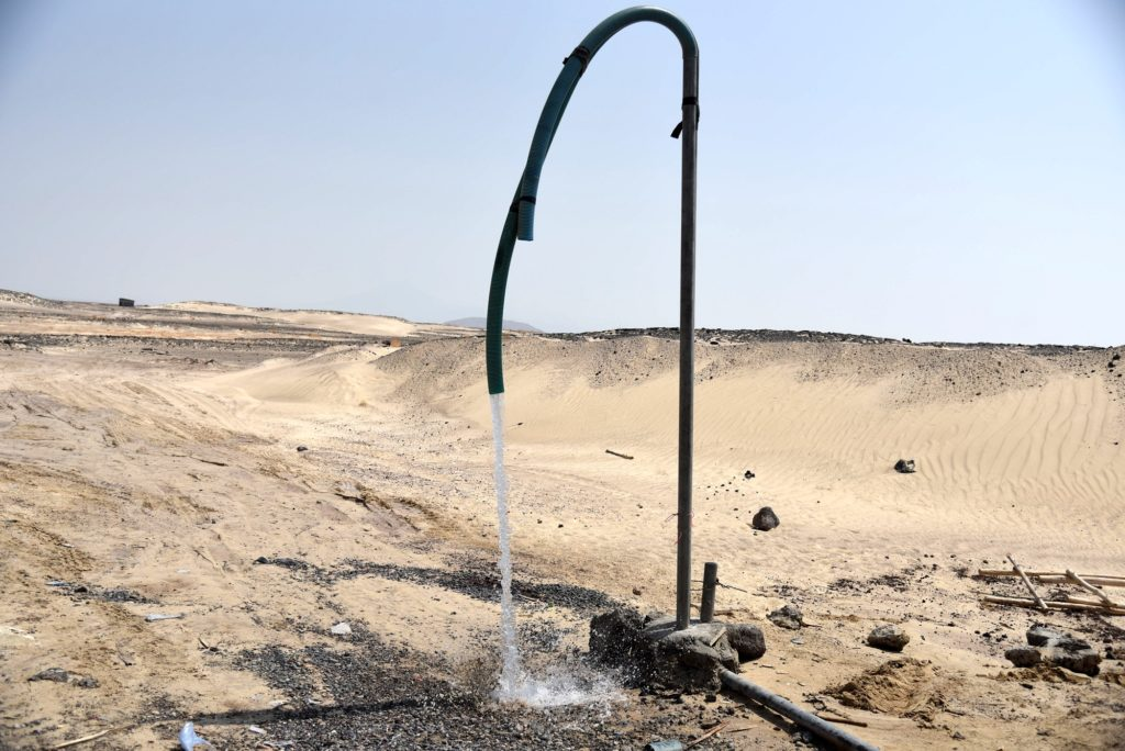 Water gushes out onto the desert floor from a hanging pipe embedded into the earth