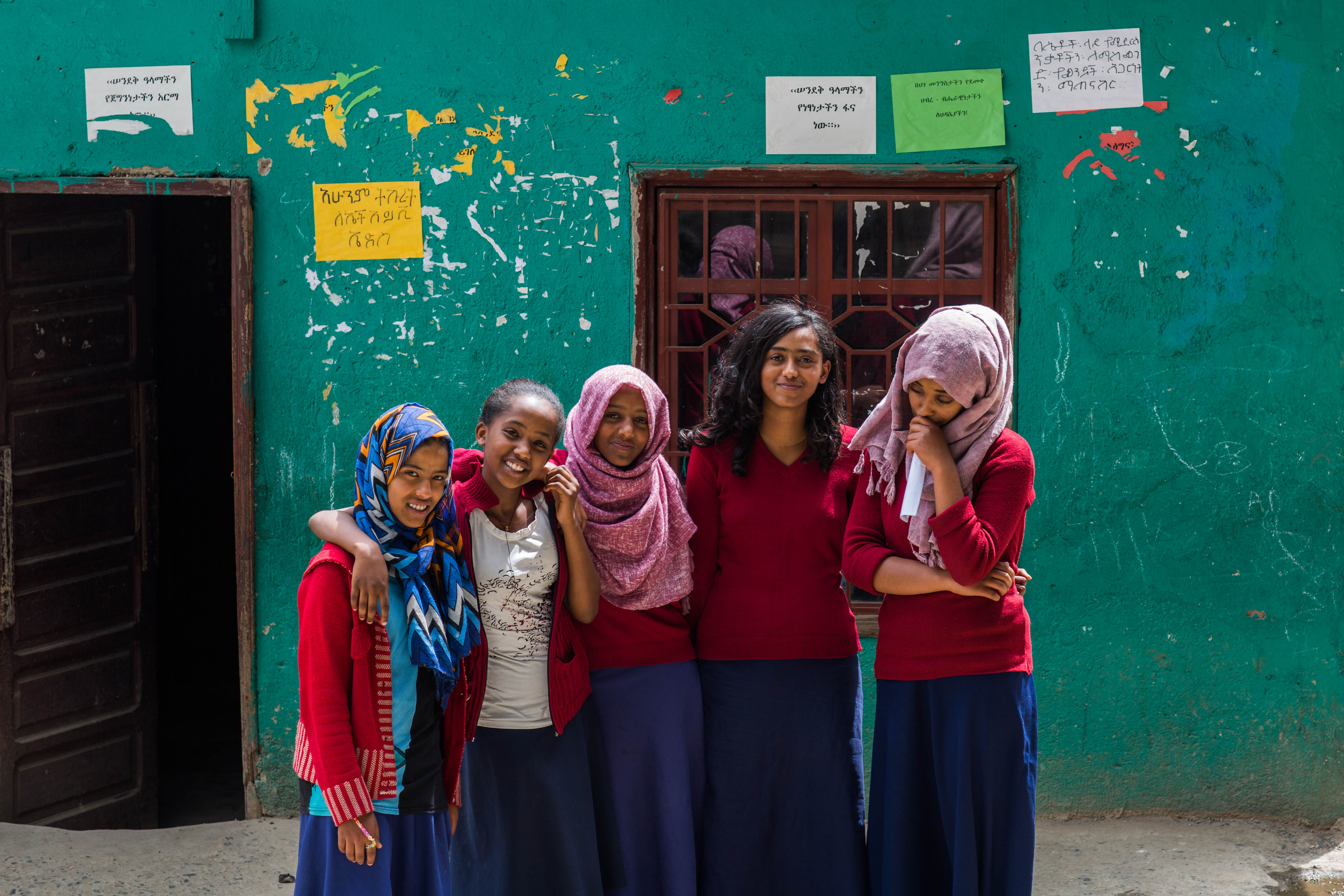 A group of five smiling school girls standing close to one another in front of a green school wall in Addis Ababa, Ethiopia