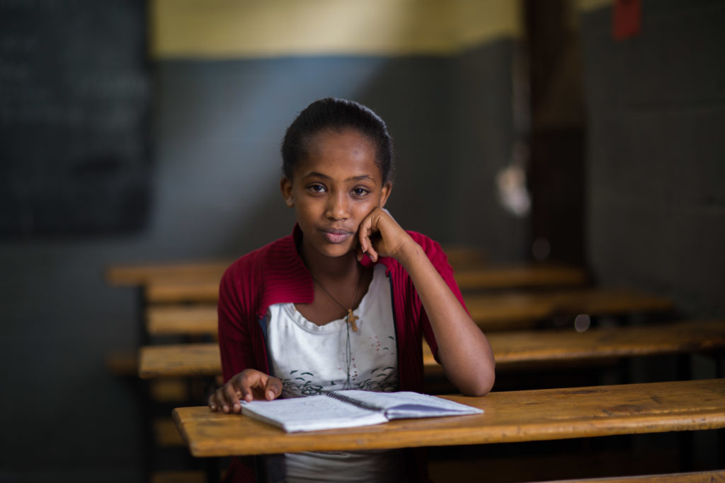 Girl sitting at school table in Ethiopia with an open notebook in front of her