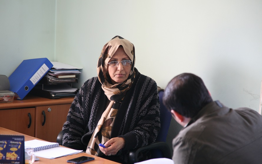 Woman with headscarf in Afghnaistan, sits at a table holding a pen, taking to a man in foreground facing her