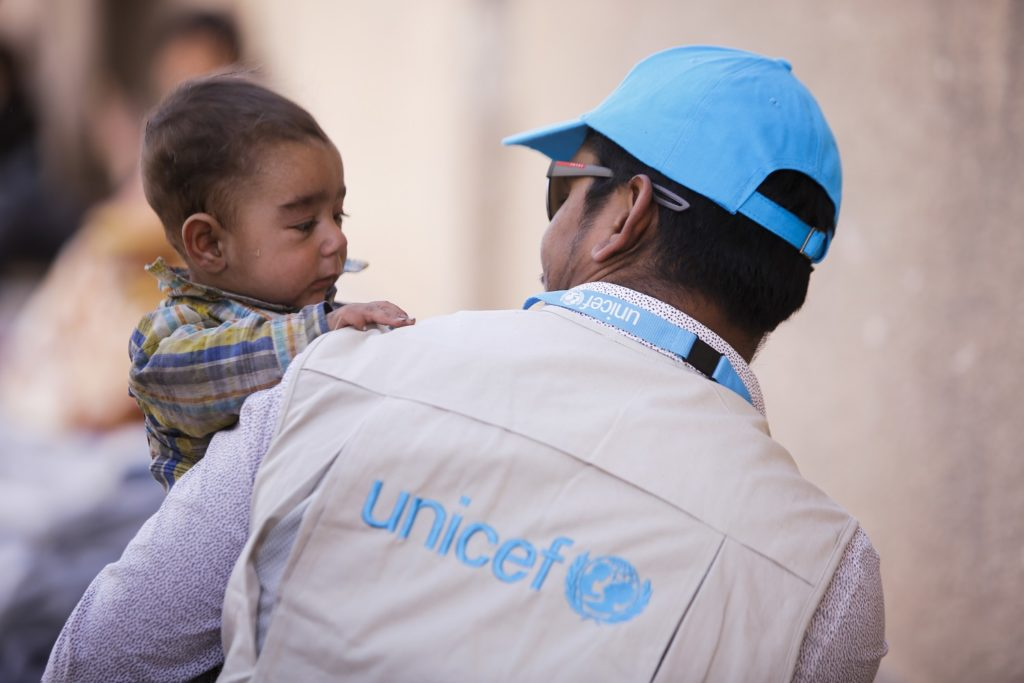 A man wearing a blue UNICEF cap and shirt with the UNICEF logo looks at the child he is holding who has his tiny hands on his shoulder, in Adra, Eastern Ghouta, Syria.