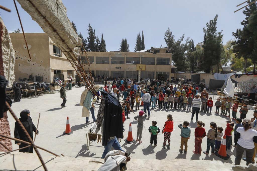 Children and elders stand in a circle in the open area of a damaged school building, with a damaged concrete beam with exposed steel rods exposed, in the foreground, in Eastern Ghouta, Syria.