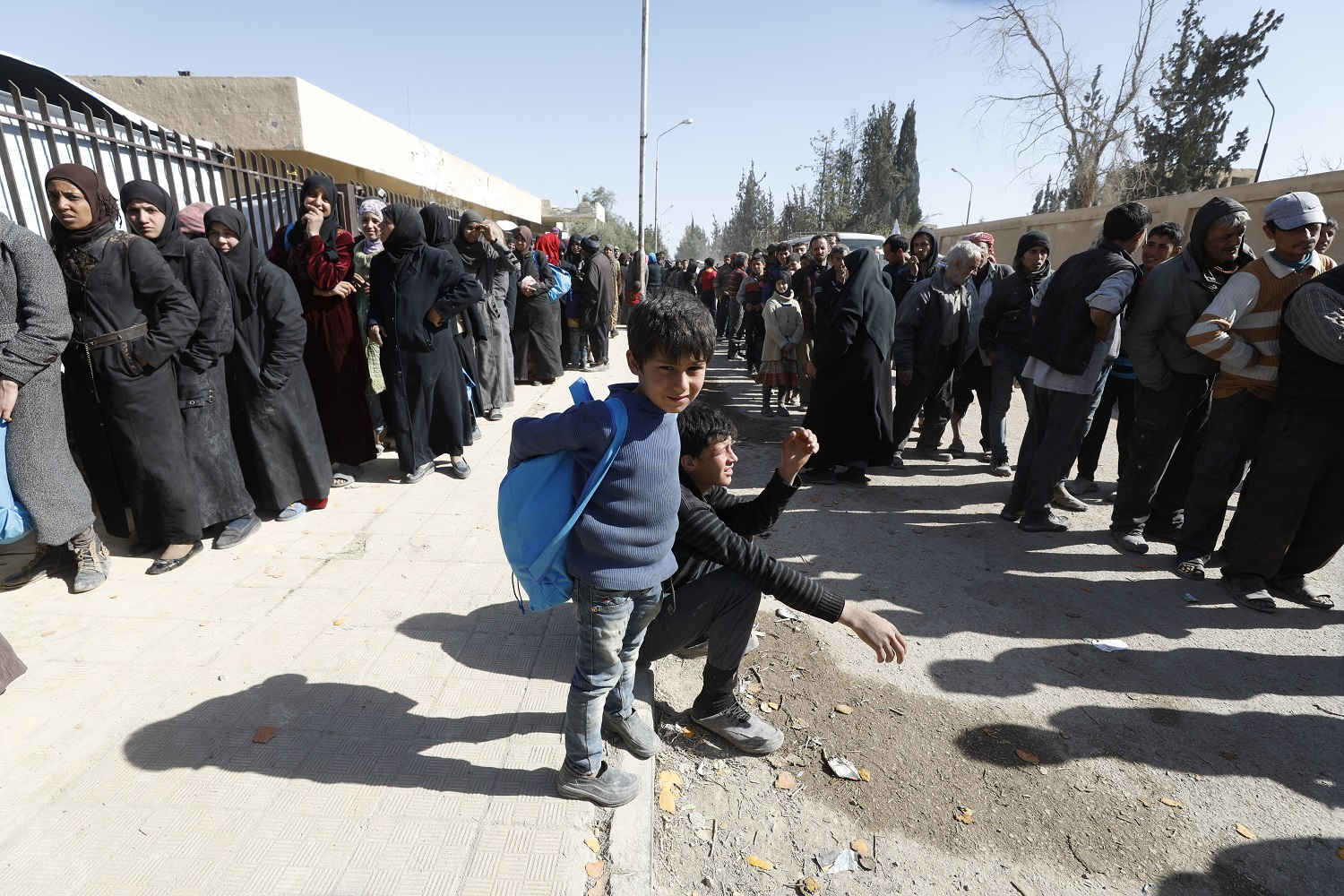 Two children - one sitting and one standing - on a pavement flanked by two rows of people - men and women in each row - in Eastern Ghouta, Syria.