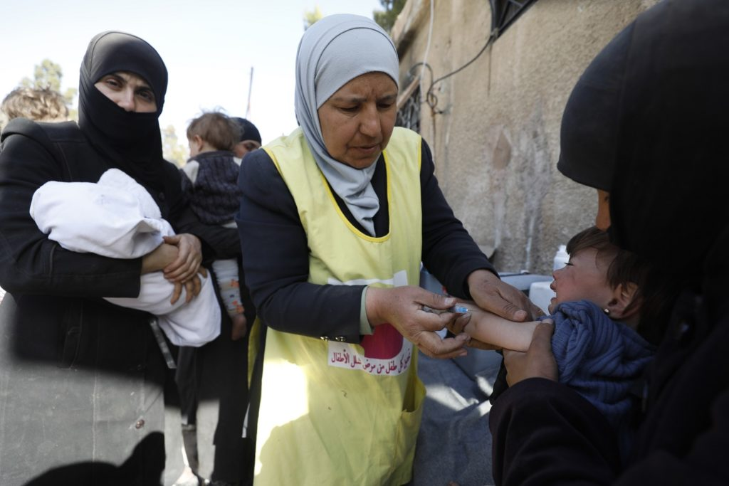A nurse holding the outstretched arm of a small child as she is about to administer an injection as her mothers look on, in Eastern Ghouta, Syria.