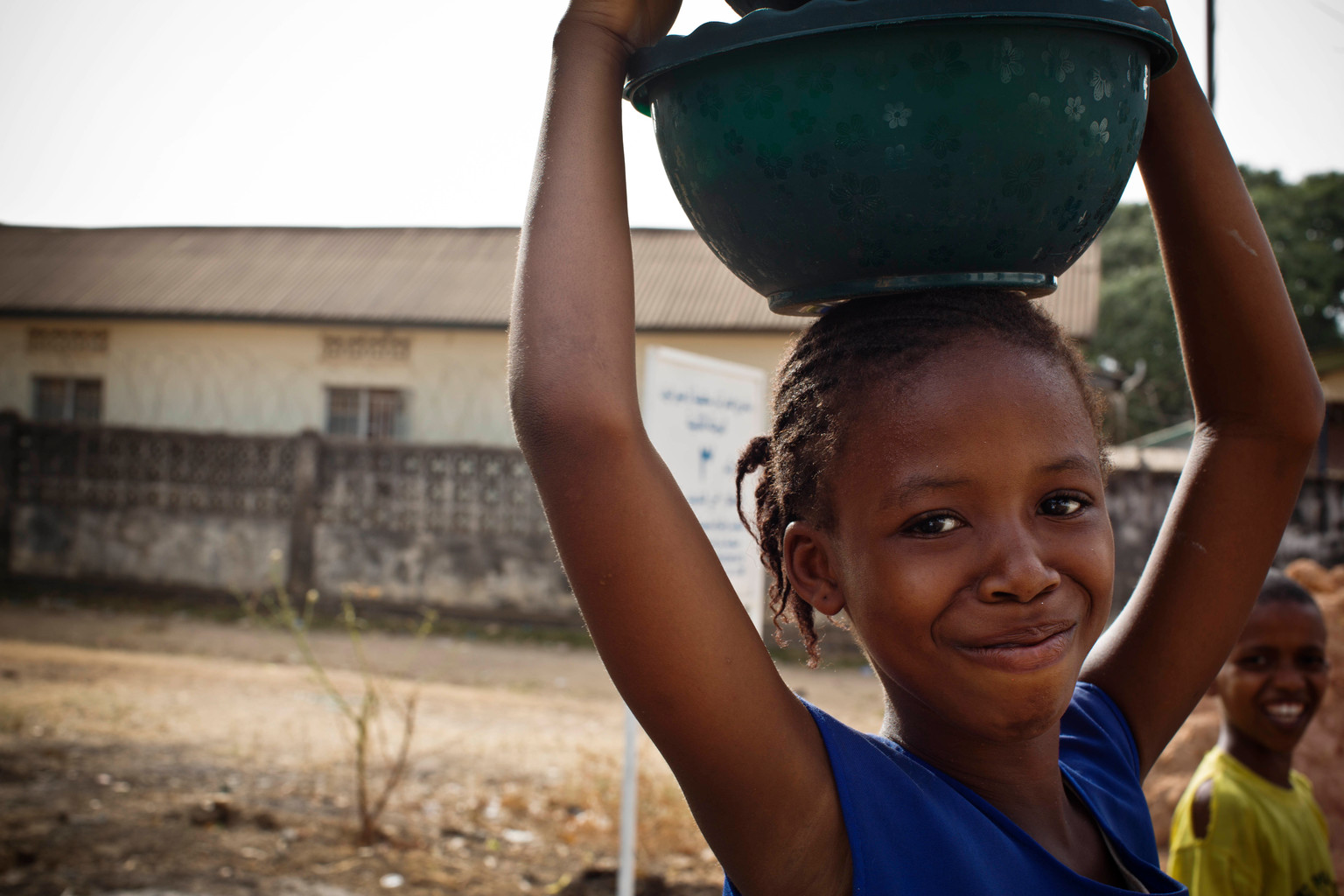 A smiling girls carries an earthern pot of water on her head.