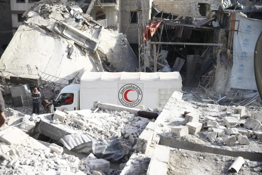 A large white van with a red crescent logo on its side makes its way through a rubble filled part of the city.