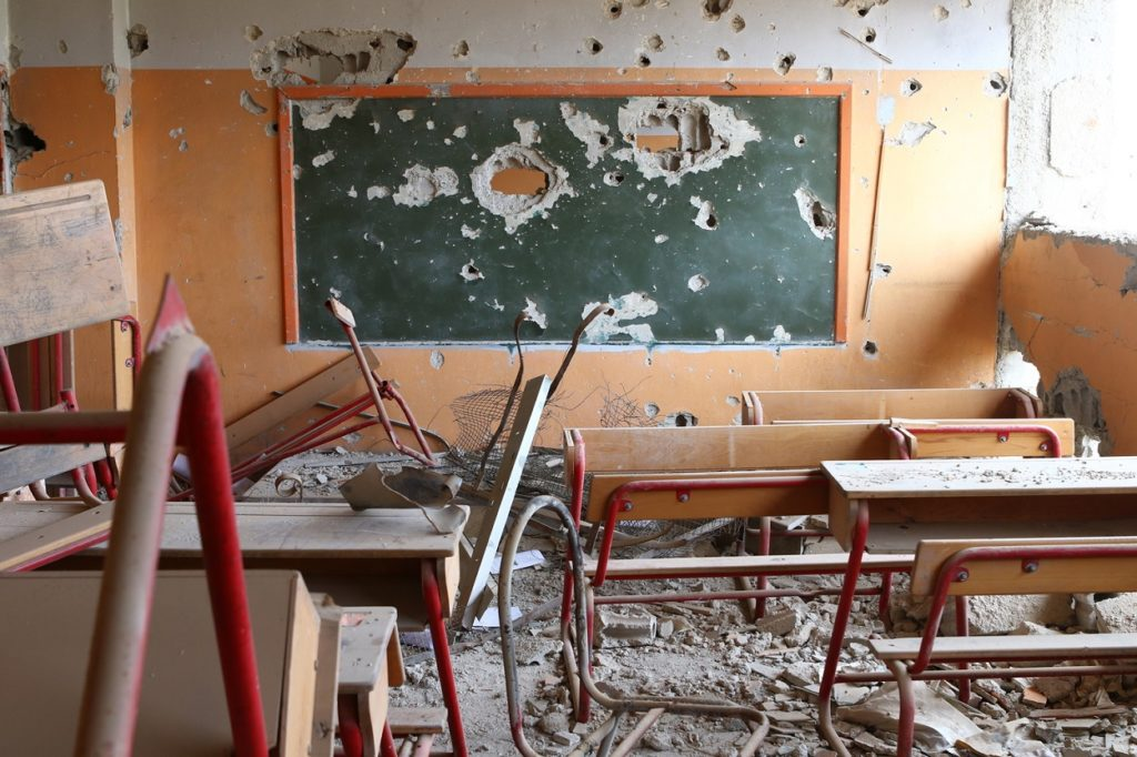 A destroyed classroom with broken benches, twisted metal, dust, and a green boadr on a wall, both riddled with holes made probably from bullets or bomb shrapnel