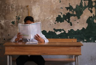 A boy sits on a school bench in a classroom with his face hidden behind a school text book that he is reading, in front of a faded green wall.