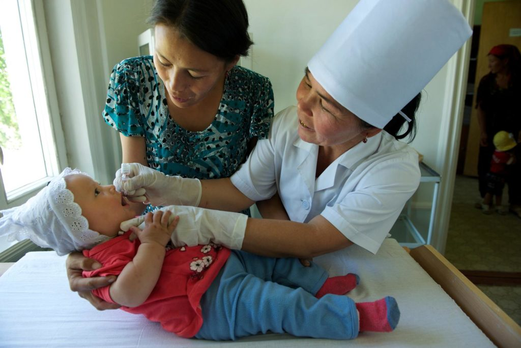 A mother holds a child on a nursing bed as a nurse administers vaccine drops.