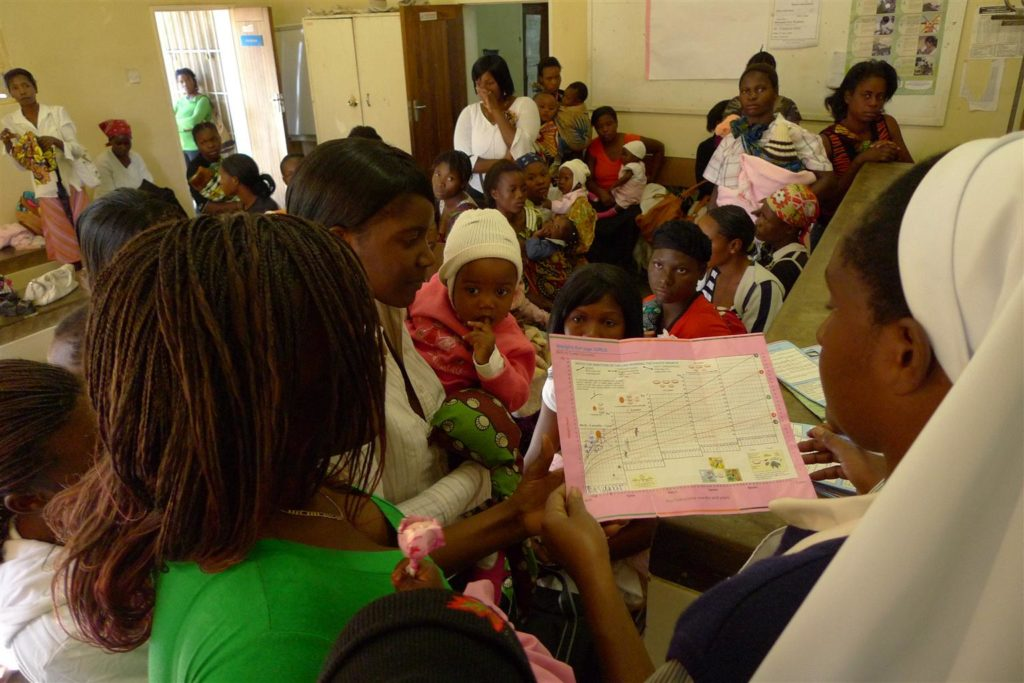 Nurse looks at graphs on a growth chart as women and children look on in a waiting room inside a clinic.