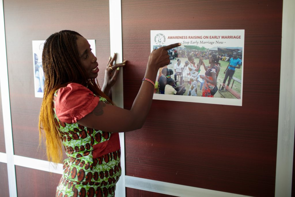 A lady points at a poster on the wall with the slogan 'Awareness Raising on early Marriage, Stop Early Marriage Now'