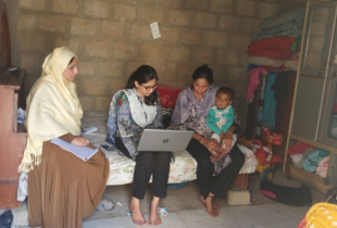 Three women sit on a bed in a room. The girl in the center has a laptop on her lap while the woman to her left is carrying a child.