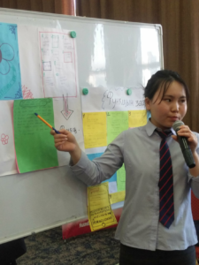 A young girl ponting at charts on a whiteboard behind her as she speaks into a microphone
