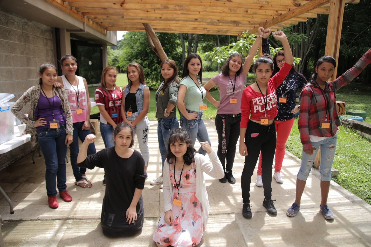 A group of Costa Rica girls stand as they strike various empowering poses.