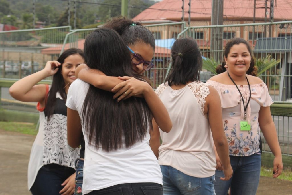 A group of Costa Rica girls stand smiling as two of them hug each other.
