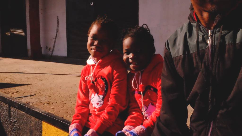 Two girls in matching red clothes smile at the camera, at a detention center in Tripoli, Libya.