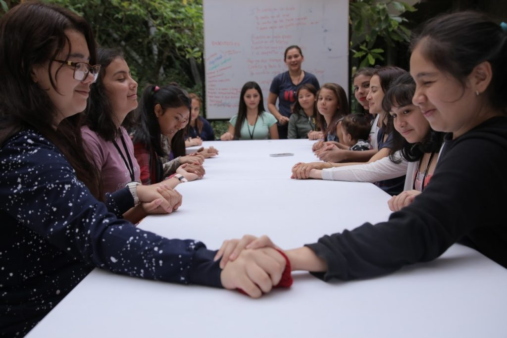 A group of young Costa Rica women sit around a table, with two of them in the foreground holding hands across the table.