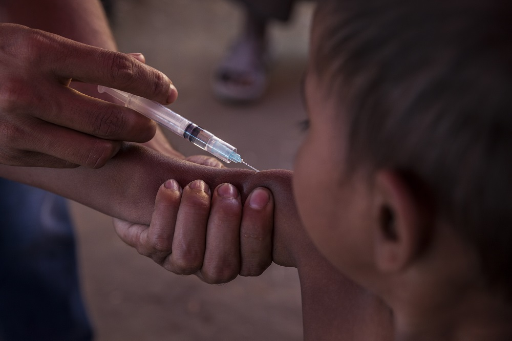 A child receives an injection in his upper arm