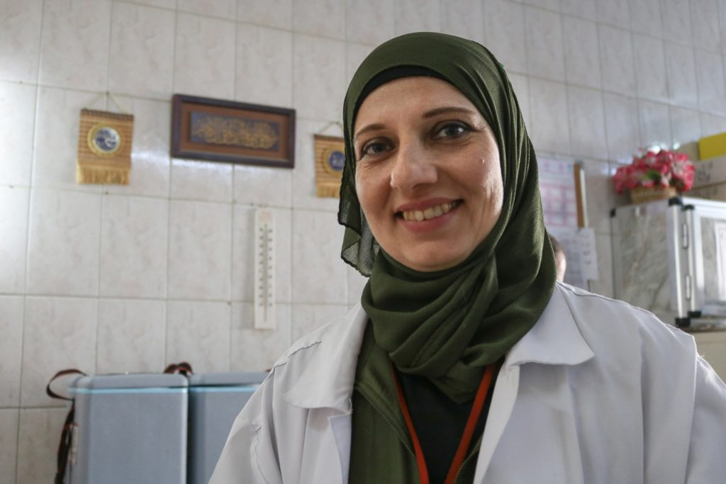 A female doctor wearing a traditional head scarf smiles.