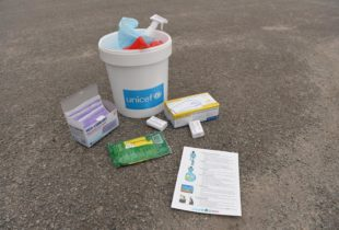 A bucket marked 'UNICEF' stands on the floor containing cleaning supplies and with other medical supplies, soaps and a pamphlet placed near it.