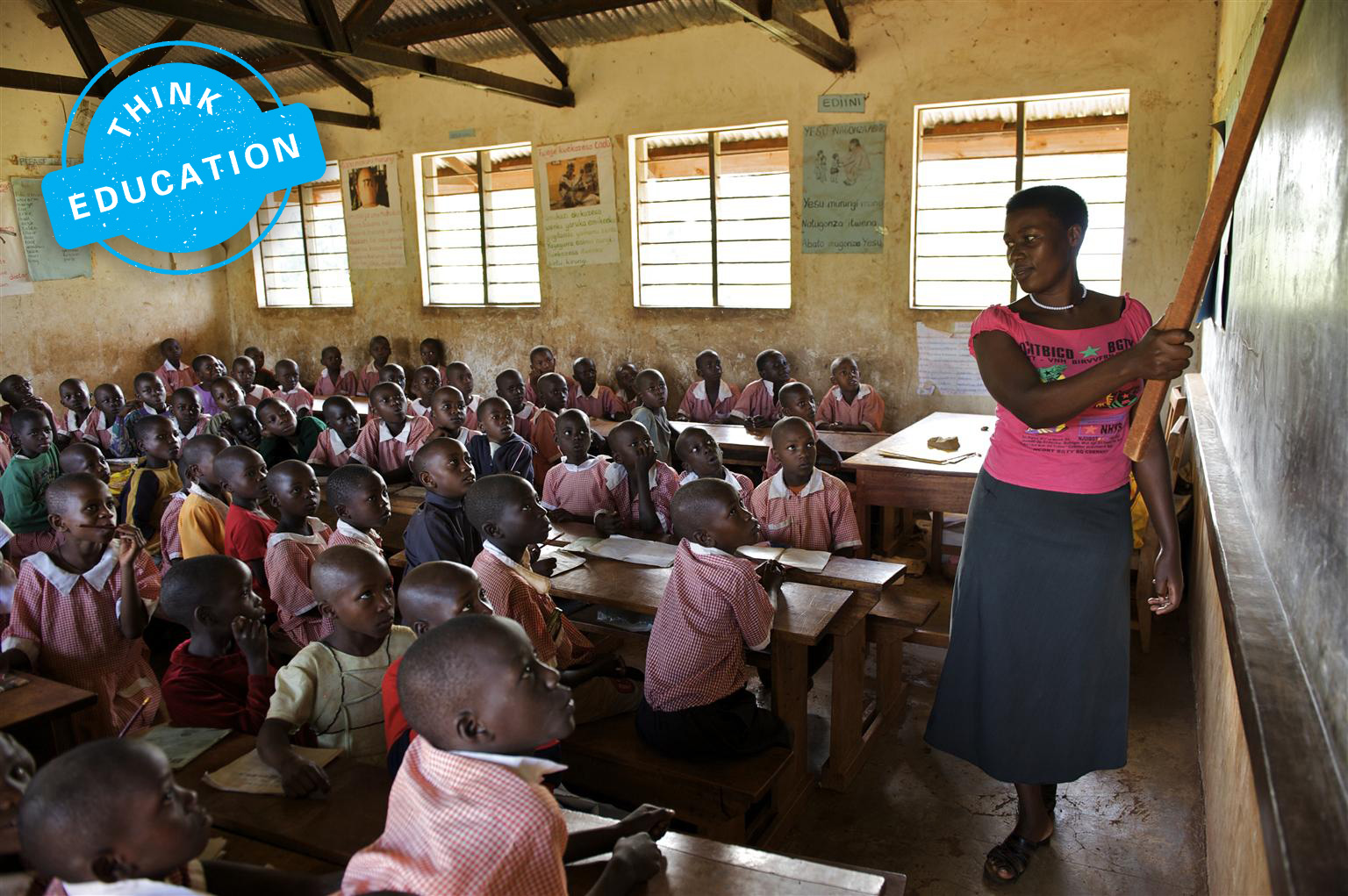 A teacher points at the blackboard with a ruler as she turns to face a classroom full of children looking attentively at her and the board. From Think Education Series of think pieces on the challenges facing global education.