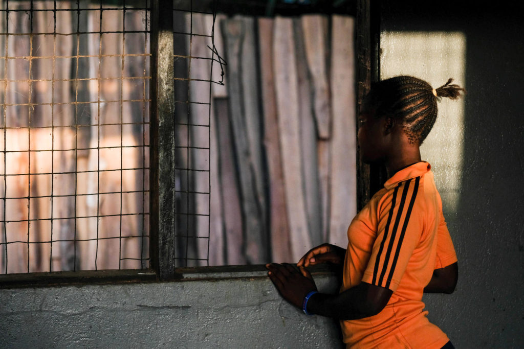 A young girl in an ornage sports tee stands looking out the window in South Sudan.
