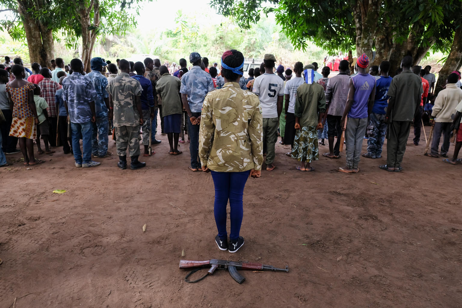 Back view of a young South Sudanese girl standing in the centre behind a group of other former child soldiers. An AK-47 rifle rests on the ground behind her.