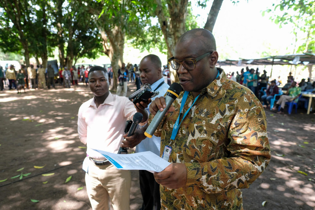 A man speaks into hand held microphones whilst reading from a paper with the UNICEF letter head. he is addressing a crowd of people sitting around him under some trees in South Sudan.